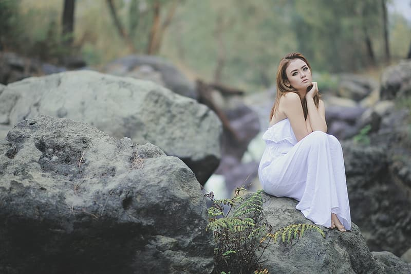 Woman wearing white strapless dress sitting on the stone