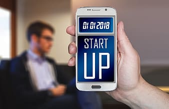 Person holding Samsung Galaxy S6 displaying startup at 01 01 2018