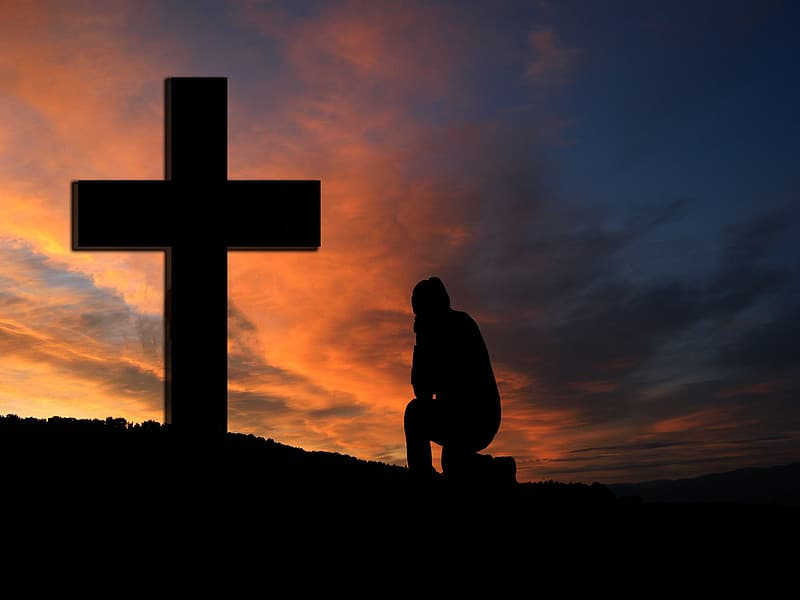 Silhouette of person sitting in front of cross