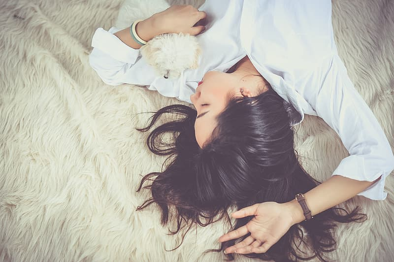 Woman in white dress shirt lying on white bed