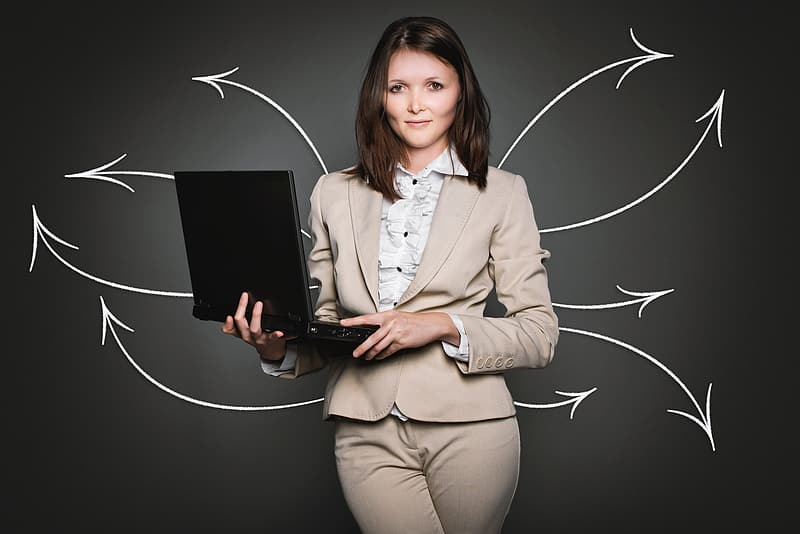 Woman wearing grey blazer and grey bottoms smiling while holding laptop computer