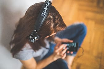 Woman wearing headphones while holding phone