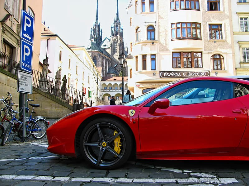 Red Ferrari sports coupe parked on bricked pavement at daytime