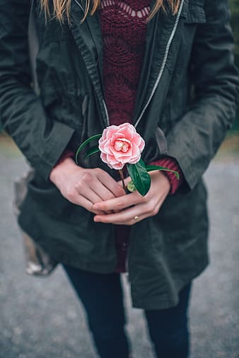 Photography of woman in black jacket holding a pink flower