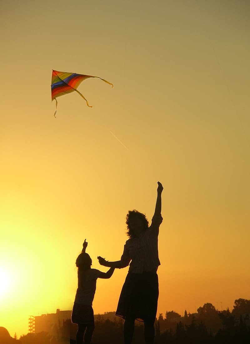 Person flying an orange, green, and blue kite