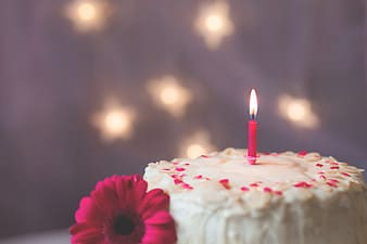 Pink candle on white icing cake