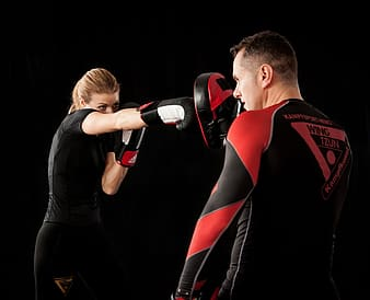 Man in black and red boxing gloves holding red and black boxing gloves