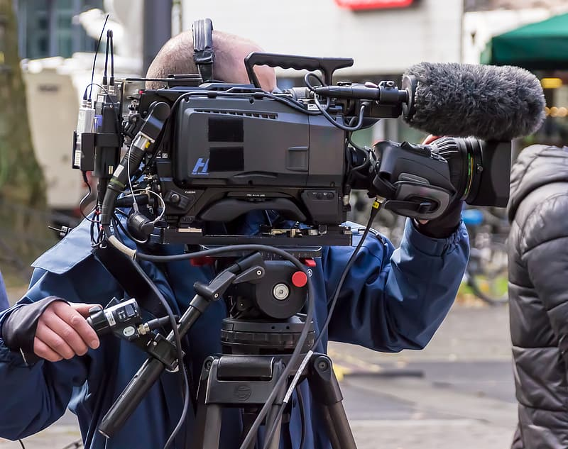 Person standing in front of professional video camera