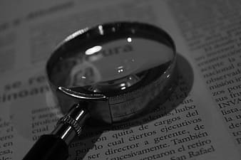Grey magnifying glass on white book