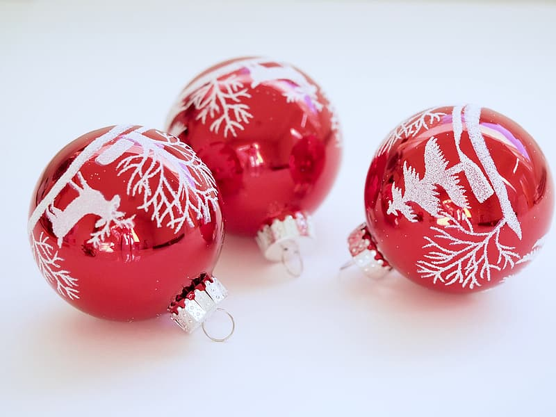 Three red-and-white Christmas baubles