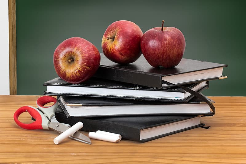 Ripe apples on notebook pile