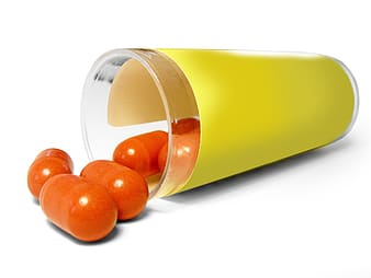 Orange pills spilled on yellow glass container