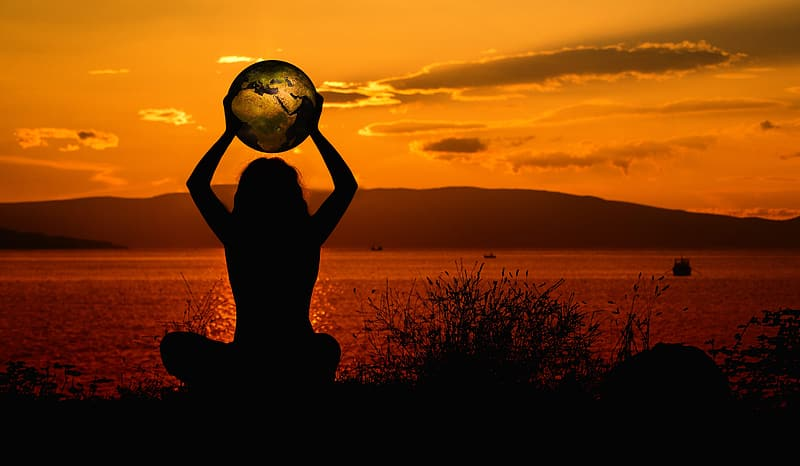 Silhouette of woman holding globe