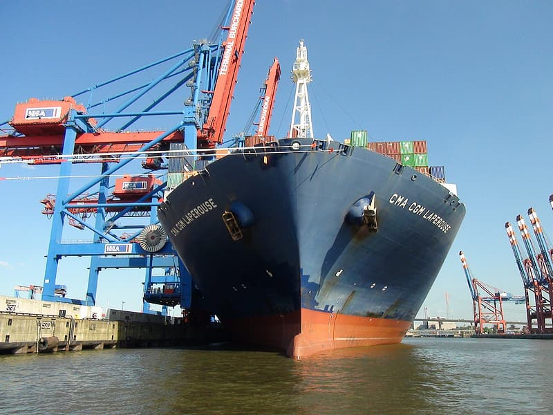 Blue and red cargo ship on dock during daytime