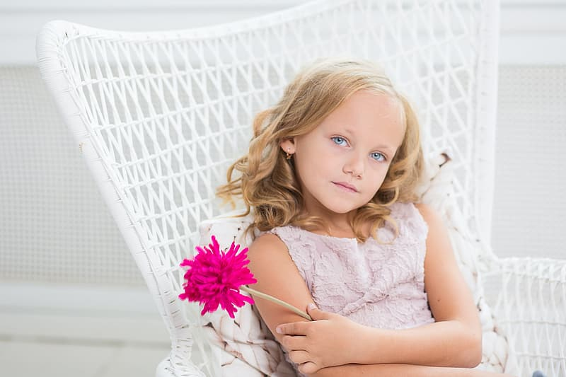 Girl wearing pink floral top holding pink flower sitting on white chair