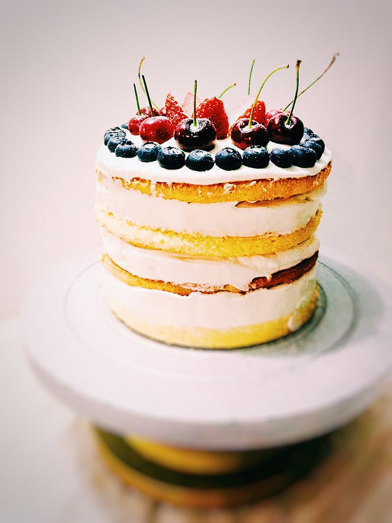 Round white coated icing cake with cherry, strawberries and cranberries on top