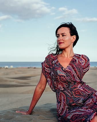 Woman in red and white floral dress standing on beach during daytime