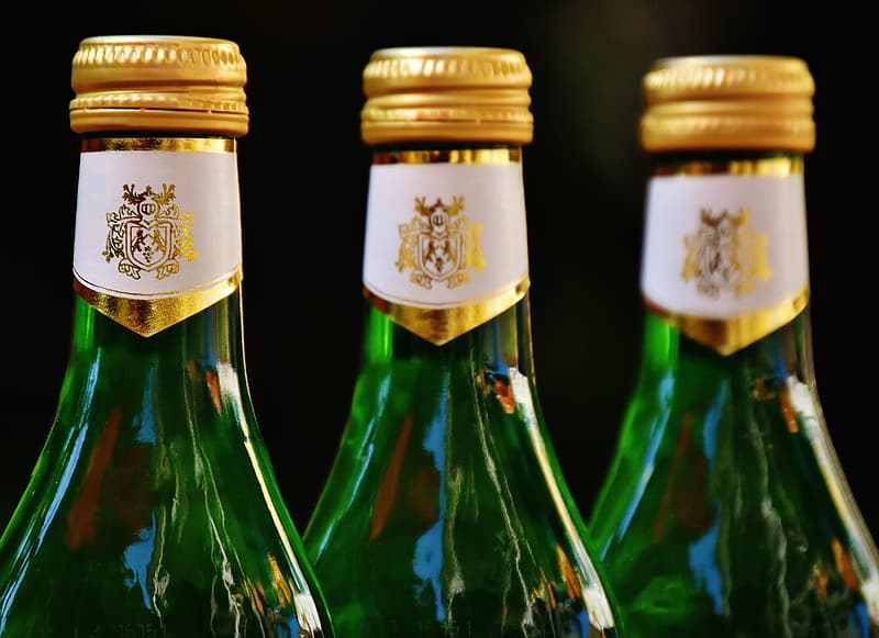 Three green glass bottles with yellow bottle caps