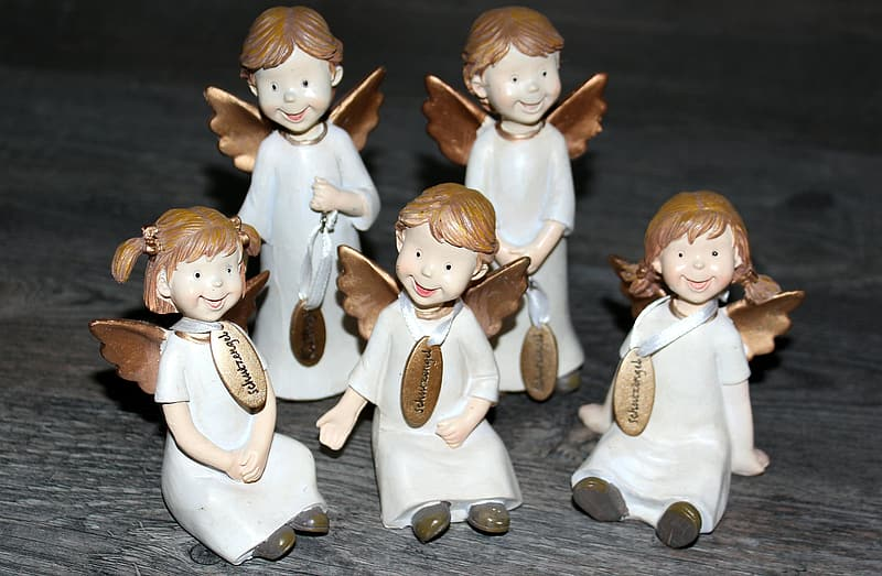 White ceramic angel figurines on gray table