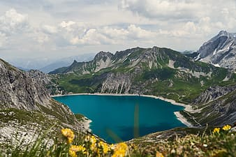 Blue lake between green mountains under white clouds and blue sky during daytime