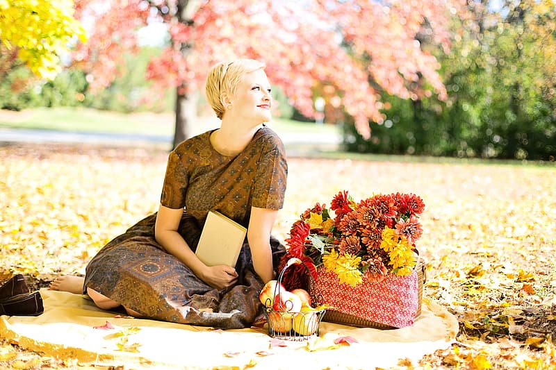 Woman wearing brown floral dress sitting beside basket of red and yellow petaled flowers