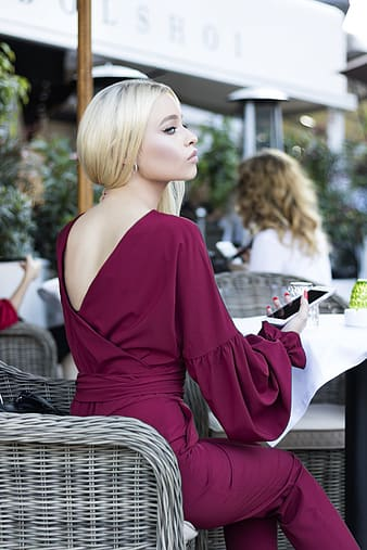 Woman sitting on wicker chair holding smartphone looking right