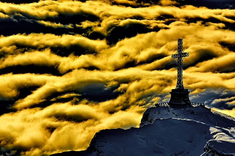 Cross statue on top of white mountain during day time