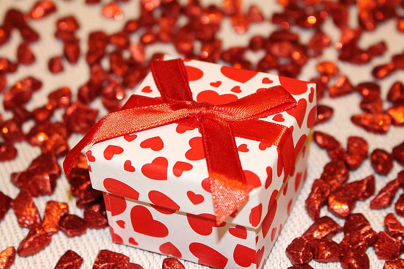 White and red heart print box with bow on white textile