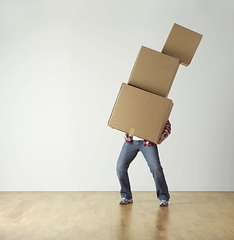Person wearing red shirt carrying three brown boxes