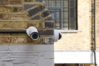Two white security cameras