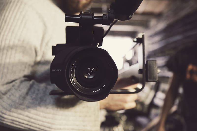 Selective focus photography of camcorder beside man's arm