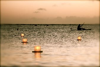 Selective silhouette phtography of candles on body of water
