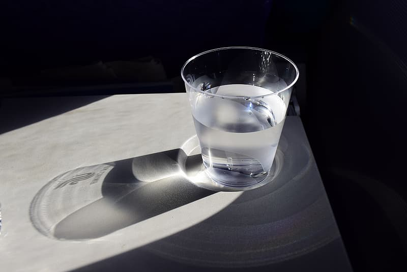 Glass cup with water on white panel