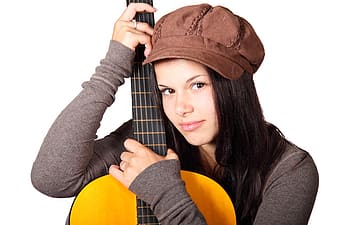 Woman wearing gray long-sleeved shirt and brown cap holding brown guitar