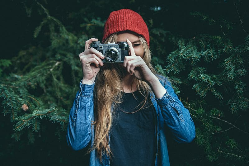 Woman wearing blue denim jacket and red beanie taking photo with grey SLR camera near green-leafed tree