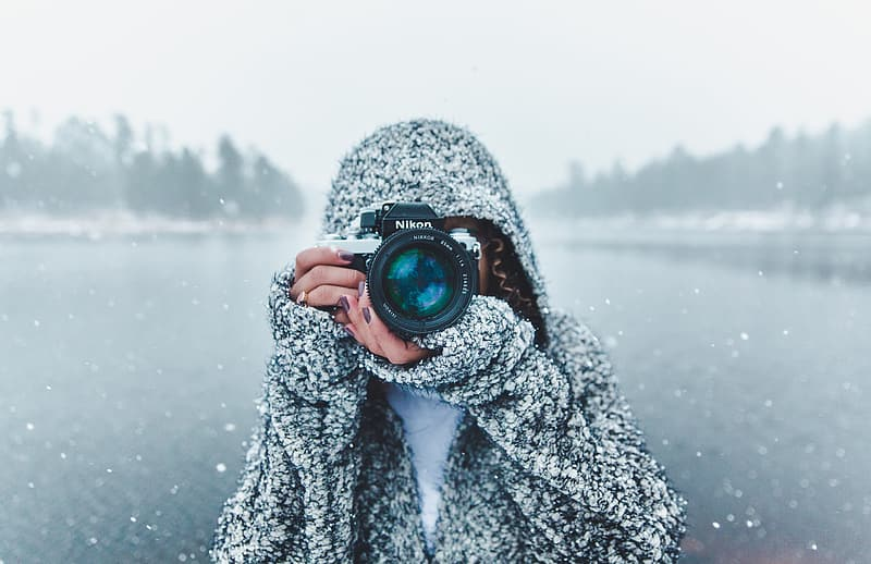 Selective focus photo of a person holding black Nikon DSLR camera about to take a picture during snow season