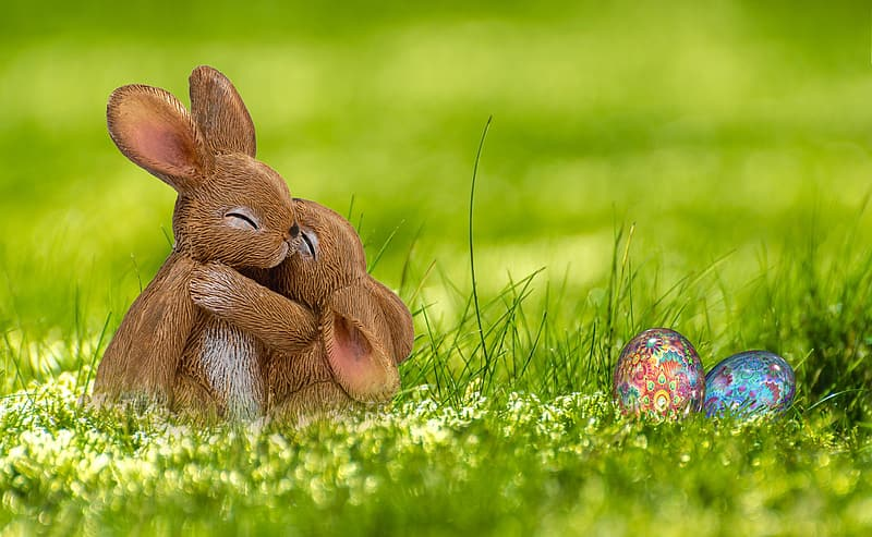 Two brown rabbits on green grass with easter eggs during daytime