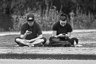 Man and woman sitting on ground in grayscale photography