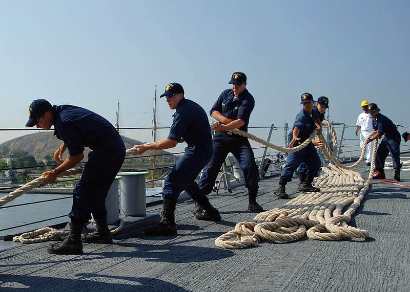 Group of men pulling rope on ship deck