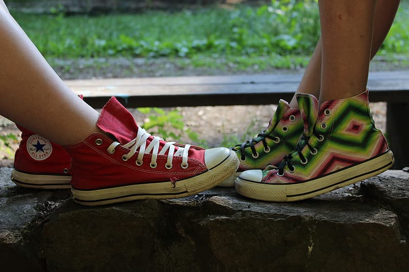 Person wearing green and red converse all star high top sneakers