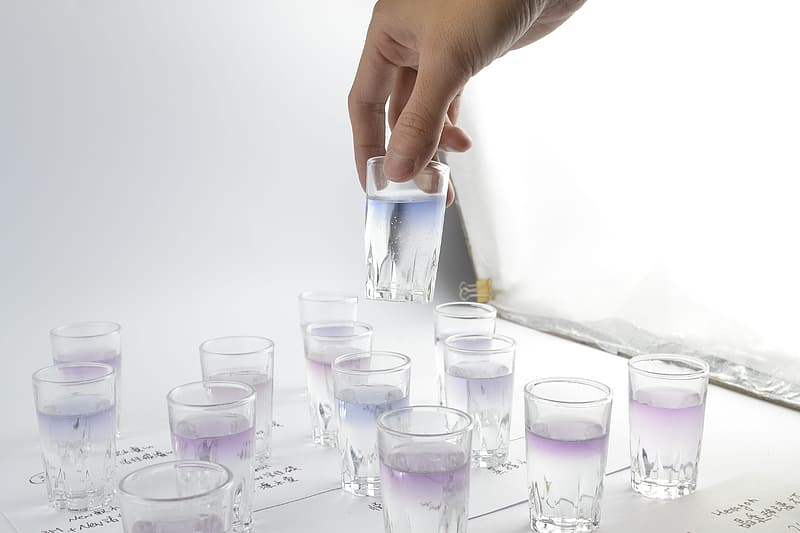 Person holding drinking glass filled with liquid