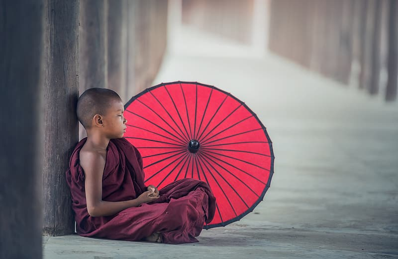 Photo of child monk in maroon robe sitting on floor beside red parasol