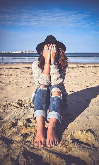 Woman in gray sweater and blue denim distressed pants covering face with hands sitting on sand near body of water