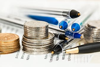 Stack of silver-colored and gold-colored coins near blue and black ballpoint pens