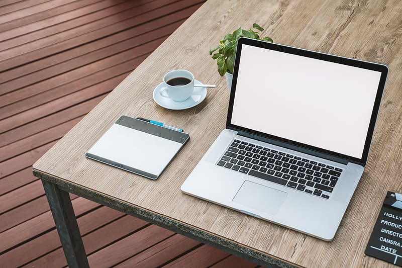 MacBook Pro turned on on top of brown wooden table near the teacup with saucer