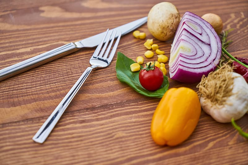 Silver metal knife and fork beside vegetables on brown wooden surface