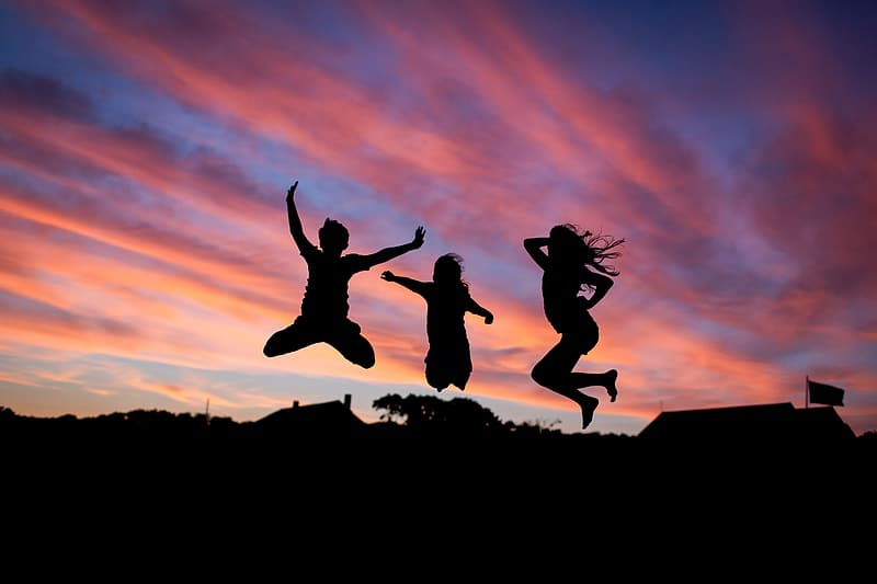 Silhouette of three people jumping during sunset