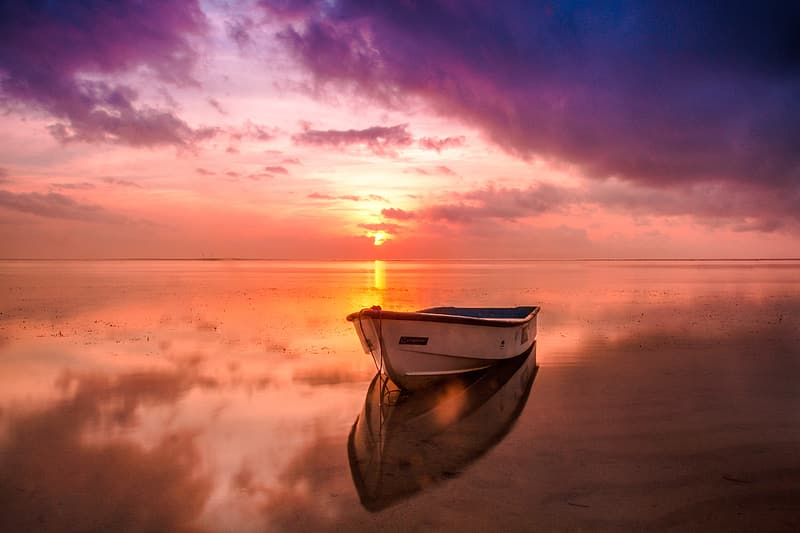 White and brown wooden boat on sea under gray clouds during sunset