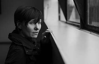 Greyscale photo of woman wearing coat looking through the window
