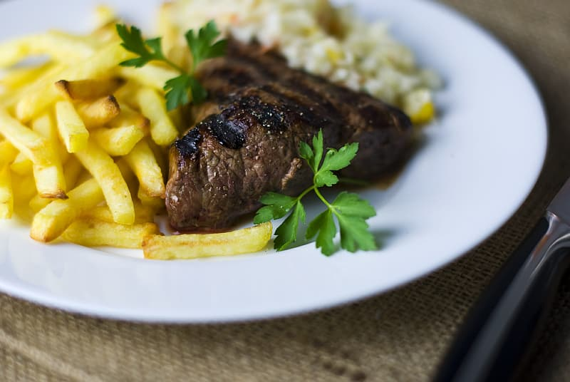 Selective focus photography of grilled meat with potato fries